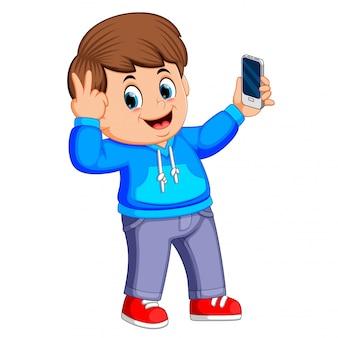 Jongen houdt zijn smartphone met zijn hand en neemt een selfie van zichzelf