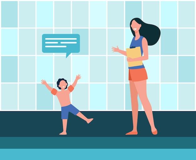 Jongen in gesprek met vrouwelijke trainer bij zwembad