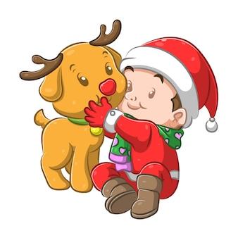 Jongen met behulp van het kerstkostuum knuffelen zijn hond