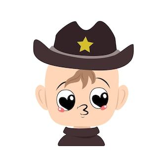 Jongen met grote hartogen en kuslippen in sheriffhoed met gele ster schattig kind met liefdevol gezicht in c...