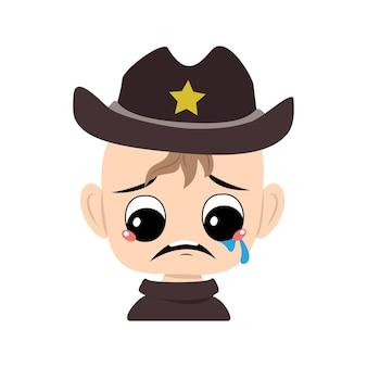 Jongen met huilen en tranen emotie verdrietig gezicht depressieve ogen in sheriff hoed met gele ster hoofd van c...