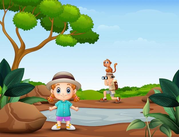 Jongen met verrekijker met een klein meisje in de natuur