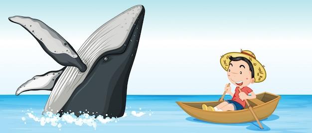Jongen op de boot naast walvis
