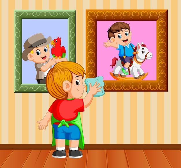 Jongen opruimen van het frame foto met de handdoek in zijn huis