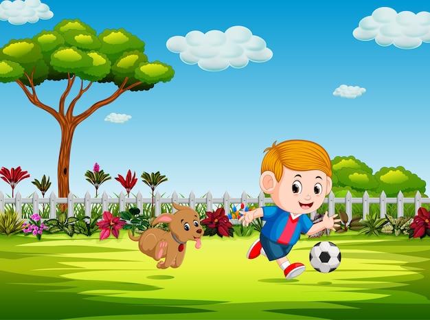 Jongen speelt voetbal in de tuin met zijn hond