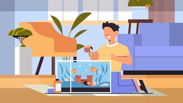 Jongen voedt vissen in aquarium huisdier vriendschap met huisdier concept woonkamer interieur