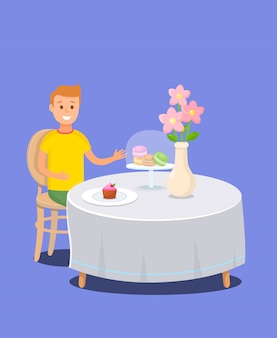 Jongen zit aan tafel in banketbakkerij met snoepjes.