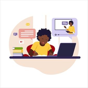 Jongen zit achter zijn bureau en studeert online