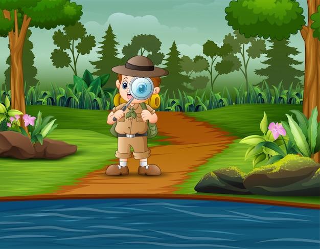 Jongensontdekkingsreiziger met vergrootglas in het bos