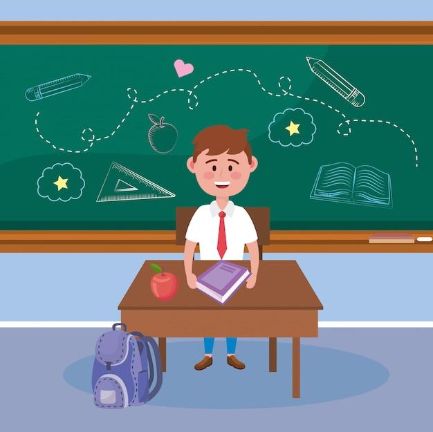Jongensstudent met appelfruit en boek in het bureau