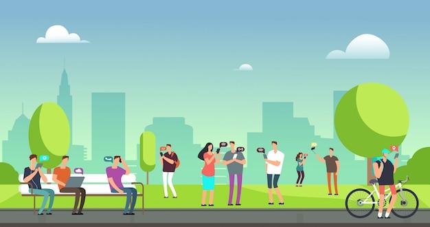 Jongeren die smartphones en tabletten gebruiken die in openlucht in park lopen.