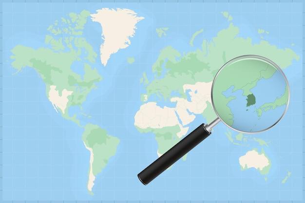 Kaart van de wereld met een vergrootglas op een kaart van zuid-korea.