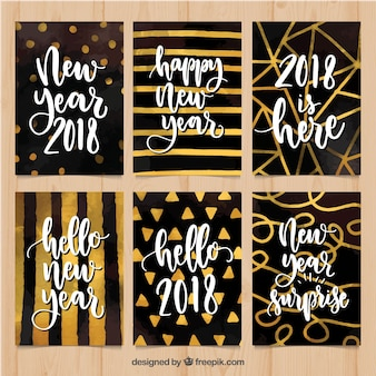 Kaarten 2018 van het waterverf nieuwe jaar in goud en zwart