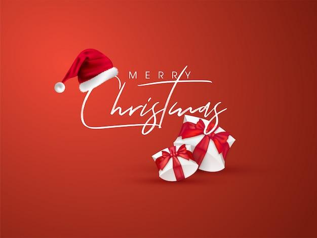 Kalligrafie tekst merry christmas met kerstmuts en geschenkdozen op oranje wenskaart.