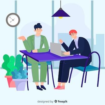 Kantoormedewerkers zitten aan een bureau en praten met elkaar