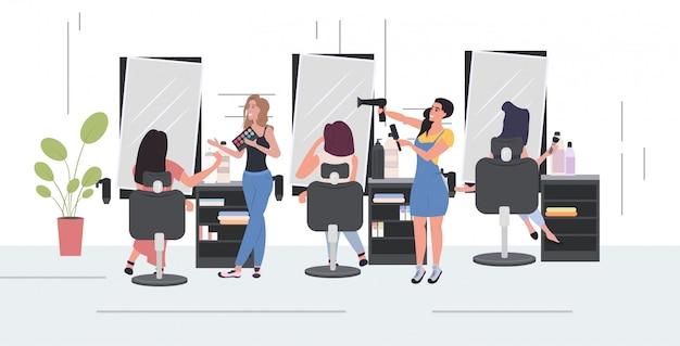 Kapper met behulp van föhn kapsel maken aan haar klant vrouwen testen oogschaduw palet schoonheidssalon interieur horizontale volledige lengte