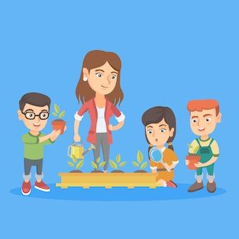 Kaukasische leraar en schoolkinderen die spruiten planten