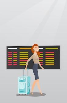 Kaukasische vrouw die met koffer bij luchthaven loopt.