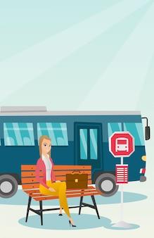 Kaukasische vrouw die op een bus bij de bushalte wacht.