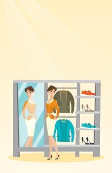 Kaukasische vrouw die op jasje in kleedkamer probeert