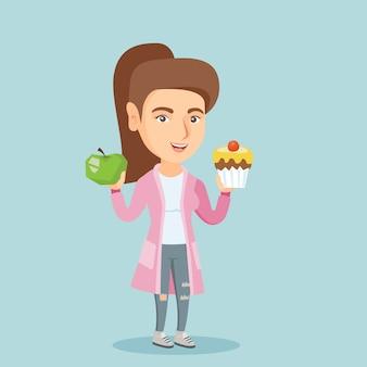 Kaukasische vrouw die tussen appel en cupcake kiest