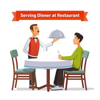 Kelner serveert zilveren schotel met deksel aan een klant