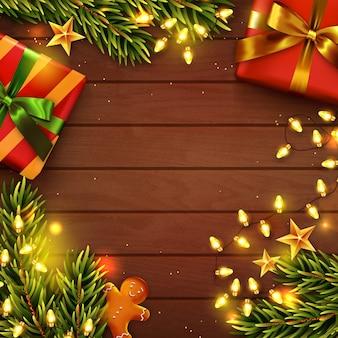 Kerst achtergrond. houten tafel versierd met geschenken, kerstboomtakken, peperkoekmannetje en guirlande lichten. bovenaanzicht.