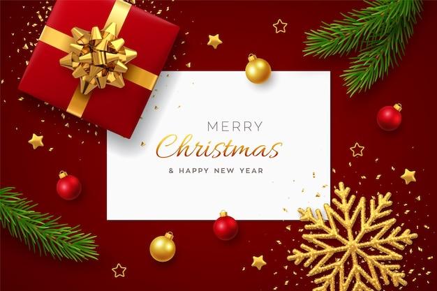 Kerst achtergrond met papieren kaart, realistische rode geschenkdoos met gouden strik, pijnboomtakken, gouden sterren en kerstballen