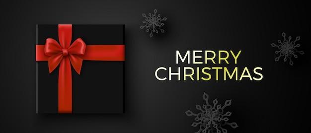 Kerst banner met zwarte geschenkdoos en rode strik