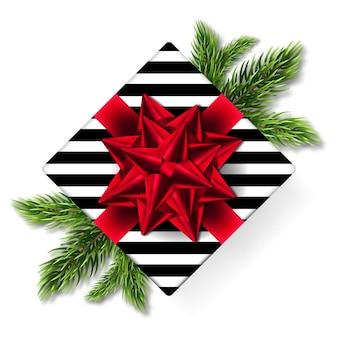 Kerst doos met een geschenk met rode bogen op vuren takken