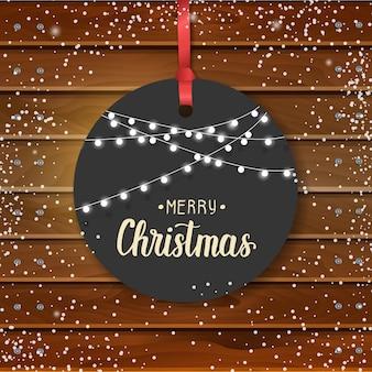 Kerst label en slingers op houten bord. gelukkig nieuwjaar. copyspace. groet