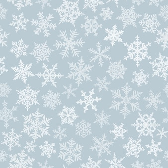 Kerst naadloos patroon met complexe grote en kleine sneeuwvlokken, wit op grijze achtergrond