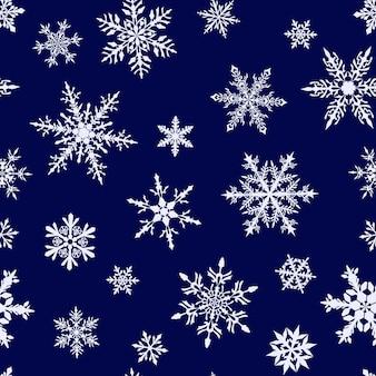 Kerst naadloos patroon van complexe grote en kleine sneeuwvlokken in witte kleuren op blauwe achtergrond