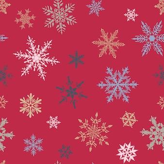 Kerst naadloos patroon van complexe grote en kleine veelkleurige sneeuwvlokken op roze achtergrond