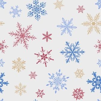 Kerst naadloos patroon van complexe grote en kleine veelkleurige sneeuwvlokken op witte achtergrond