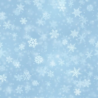 Kerst naadloos patroon van complexe wazige en heldere vallende sneeuwvlokken in lichtblauwe kleuren met bokeh-effect