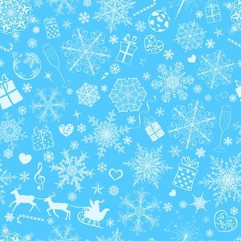Kerst naadloos patroon van grote en kleine sneeuwvlokken en verschillende kerstsymbolen, wit op blauw