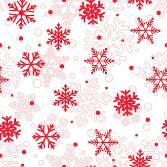 Kerst naadloos patroon van grote en kleine sneeuwvlokken, rood op wit