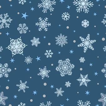 Kerst naadloos patroon van grote en kleine sneeuwvlokken, wit op blauw