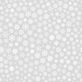Kerst naadloos patroon van kleine sneeuwvlokken, wit op grijs