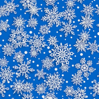 Kerst naadloos patroon van papieren sneeuwvlokken met zachte schaduwen op blauwe achtergrond