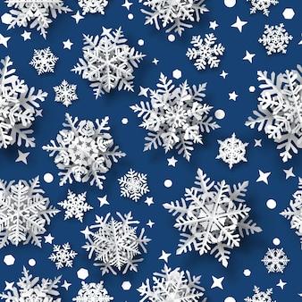 Kerst naadloos patroon van papieren sneeuwvlokken met zachte schaduwen, wit op blauwe achtergrond