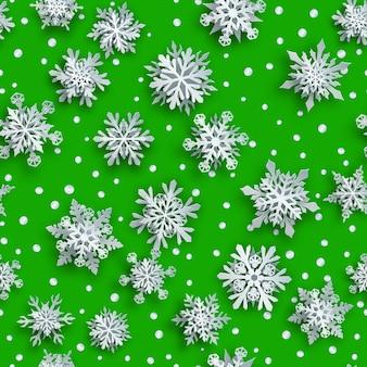 Kerst naadloos patroon van witte complexe papieren sneeuwvlokken met zachte schaduwen op groene achtergrond