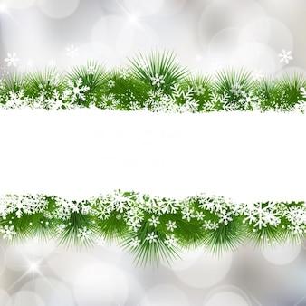 Kerst sneeuwvlokken bokeh achtergrond met bladeren