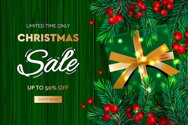 Kerst verkoop banner. realistische dennentakken met bessen en groene geschenkdoos