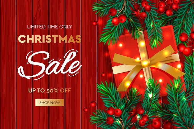 Kerst verkoop banner. realistische dennentakken met bessen en rode geschenkdoos