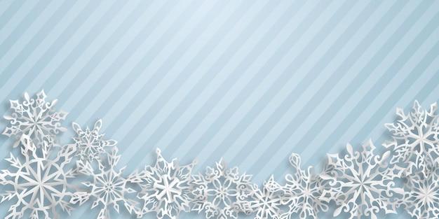 Kerstachtergrond met papieren sneeuwvlokken met zachte schaduwen op lichtblauw gestreepte achtergrond