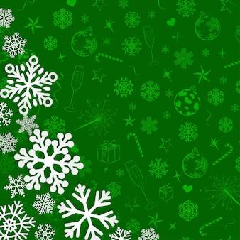 Kerstachtergrond met sneeuwvlokken die uit papier zijn gesneden op een groene achtergrond van kerstsymbolen