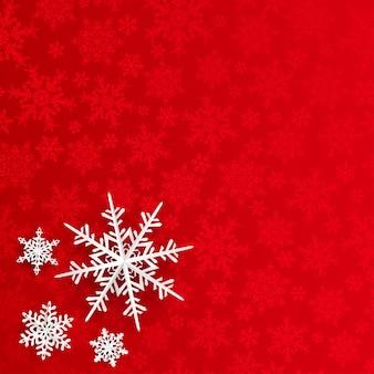 Kerstachtergrond met sneeuwvlokken die uit papier zijn gesneden op een rode achtergrond van kleine sneeuwvlokken