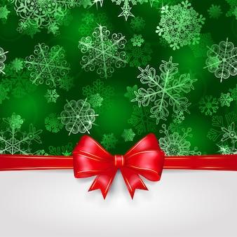 Kerstachtergrond met sneeuwvlokken in groene kleuren en grote rode strik met horizontale linten
